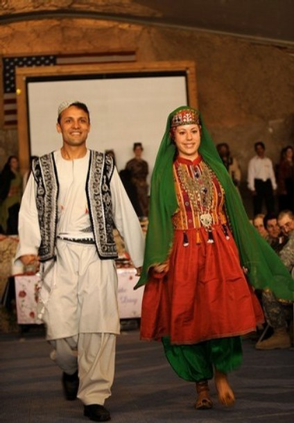 An Afghan boy, along with a US soldier wearing traditional Afghan dress, walk during a fashion show in the run up to Women���s Day at the Bagram Airbase some 50 kms north of Kabul on March 3, 2008. International Women's Day, which is celebrated on March 8 each year, is an occasion marked by women around the world and is also commemorated at the United Nations. AFP PHOTO/Massoud Hossaini (Photo credit should read SHAH MARAI/AFP/Getty Images)